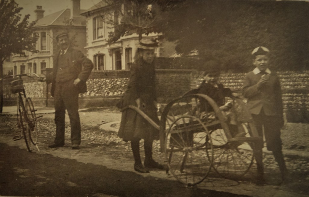 Fig. 2:  Taken in the early 1890s, at around the time of their road accident in Chapel Road, this image shows Arthur, far right, with his older sister Mary, their younger brother Gordon, sitting on the cart, and their father Arthur George senior, standing with his bicycle. The location is thought to be North Street, Worthing.